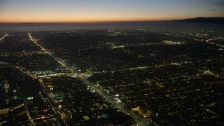 AX64_0287 - 5K stock footage aerial video of city traffic on Venice Boulevard, Palms, Los Angeles, California, twilight