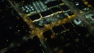 AX64_0288 - 5K stock footage aerial video bird's eye view of Washington Boulevard and a strip mall, Palms, Los Angeles, California, night