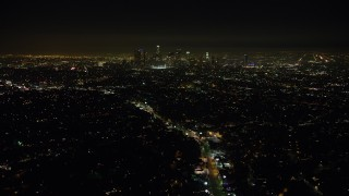 AX64_0346 - 5K stock footage aerial video of a view of the Downtown Los Angeles skyline and surrounding city sprawl, California, night