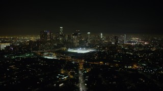 AX64_0355 - 5K stock footage aerial video approach sports fields and Downtown Los Angeles skyline at night, California