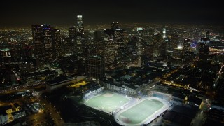 AX64_0356 - 5K stock footage aerial video fly over high school sports fields to approach Downtown Los Angeles skyscrapers, California, night