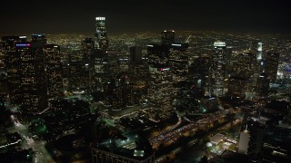 AX64_0357 - 5K stock footage aerial video flying over Westin Bonaventure to approach Downtown Los Angeles skyscrapers, California, night