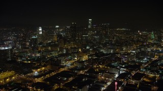 AX64_0360 - 5K stock footage aerial video reverse view of office buildings and Downtown Los Angeles skyscrapers, California, night