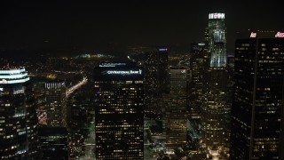 AX64_0366 - 5K stock footage aerial video of flying over tall skyscrapers in Downtown Los Angeles, California, night