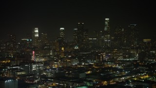 AX64_0388 - 5K stock footage aerial video Bendix Sign and Downtown Los Angeles skyline, California, night