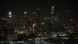 AX64_0389 - 5K stock footage aerial video approach the Bendix Sign and the Downtown Los Angeles skyline, California, night