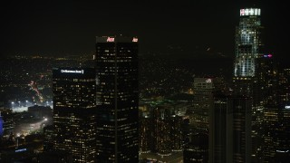 AX64_0392 - 5K stock footage aerial video approach Aon Center and tilt to Westin Bonaventure Hotel, Downtown Los Angeles, California, night