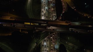 AX64_0398 - 5K stock footage aerial video tilt to a bird's eye view of cars on the 110 and 101 interchange, Downtown Los Angeles, California, night