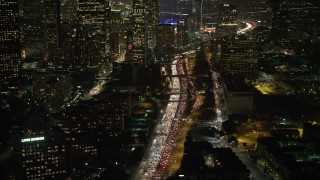 AX64_0402 - 5K stock footage aerial video tilt to heavy traffic on Highway 110, Downtown Los Angeles, California, night