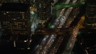 AX64_0405 - 5K stock footage aerial video of bird's eye view of heavy traffic on Highway 110, Downtown Los Angeles, California, night