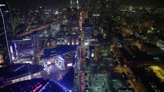 AX64_0408 - 5K stock footage aerial video tilt from Staples Center arena to reveal skyscrapers in Downtown Los Angeles, California, night
