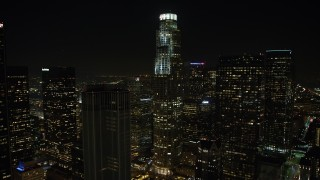 AX64_0411 - 5K stock footage aerial video tilt from US Bank Tower to reveal part of the LA Public Library at night in Downtown Los Angeles, California, night