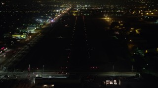 AX64_0446 - 5K stock footage aerial video of approaching Whiteman Airport runway at night, Pacoima, California