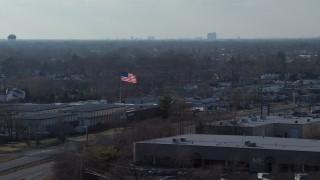 AX65_0001 - 5K stock footage aerial video of an American flag flying over warehouse buildings in Farmingdale, Long Island, New York
