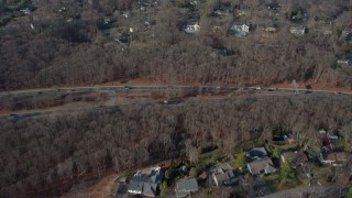 AX65_0008 - 5K stock footage aerial video bird's eye view of suburban homes, leafless trees, and highway in Plainview, Long Island, New York, winter