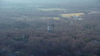 AX65_0018 - 5K stock footage aerial video fly over leafless trees to approach a water tower in Brookville, Long Island, New York, winter