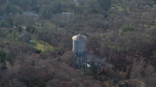AX65_0019 - 5K stock footage aerial video approach and fly over a water tower in Brookville, Long Island, New York, winter
