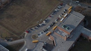 AX65_0026 - 5K stock footage aerial video tilt to bird's eye view of school busses at Great Neck North Middle School, Long Island, New York, winter