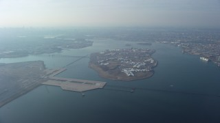 AX65_0035 - Aerial stock footage of Rikers Island on the East River as a commercial jet approaches LaGuardia Airport, Queens, New York City, winter
