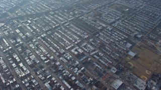 AX65_0040 - Aerial stock footage of Tilt from a bird's eye view of urban neighborhoods to reveal bridges spanning the East River in Queens, New York City, winter