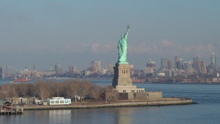 AX65_0080 - 5K stock footage aerial video orbit the torch side of the Statue of Liberty, New York, reveal Lower Manhattan skyscrapers in the background, winter