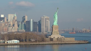AX65_0081 - 5K stock footage aerial video of Statue of Liberty, with Freedom Tower and Lower Manhattan skyline in the background, New York City, winter