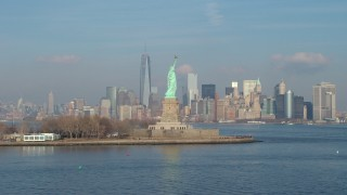 AX65_0082 - 5K stock footage aerial video flyby Statue of Liberty to focus on Freedom Tower and Lower Manhattan skyline in the distance, New York City, winter