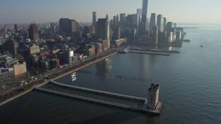 AX65_0090 - 5K stock footage aerial video tilt from Pier 34 to approach World Trade Center skyline in Lower Manhattan, New York City, winter