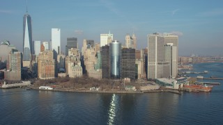 AX65_0099 - 5K stock footage aerial video flyby Battery Park, Lower Manhattan skyline, and the Staten Island Ferry Terminal, New York City, winter
