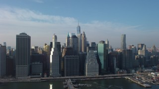 AX65_0103 - 5K stock footage aerial video of Lower Manhattan skyscrapers and East River piers, Freedom Tower in the distance, New York City, winter
