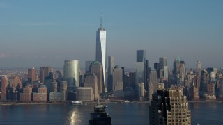 AX65_0128 - Aerial stock footage of Freedom Tower and Lower Manhattan skyline seen from across the Hudson River, New York City, winter
