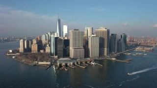 AX65_0141 - 5K stock footage aerial video of Battery Park, riverfront skyscrapers, and the Staten Island Ferry Terminal in Lower Manhattan, New York City, winter