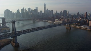 AX65_0146 - 5K stock footage aerial video of Manhattan Bridge with the Lower Manhattan skyline and the Brooklyn Bridge in the background, New York City, winter