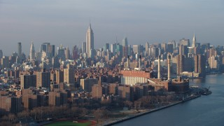 AX65_0159 - 5K stock footage aerial video of Empire State Building and Midtown Manhattan skyline seen from power plant by East River, New York City, winter