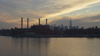 AX65_0169 - 5K stock footage aerial video fly low by an East Village power plant with Lower Manhattan skyline in the distance, New York City, winter, sunset