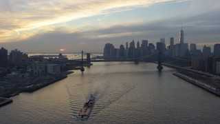 AX65_0175 - 5K stock footage aerial video fly over barge on East River to approach Lower Manhattan skyline and Manhattan Bridge, New York City, winter, sunset