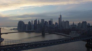 AX65_0177 - 5K stock footage aerial video approach the Brooklyn Bridge and Lower Manhattan skyline from Manhattan Bridge, New York City, winter, twilight