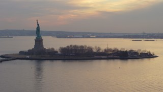 AX65_0184 - 5K stock footage aerial video of flying by the Statue of Liberty and Liberty Island in New York, winter, twilight