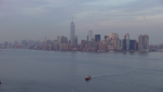 AX65_0189 - 5K stock footage aerial video of Lower Manhattan skyline seen from New York Harbor, New York City, winter, twilight