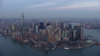 AX65_0214 - 5K stock footage aerial video of flying by Battery Park and Lower Manhattan skyscrapers in New York City, winter, twilight