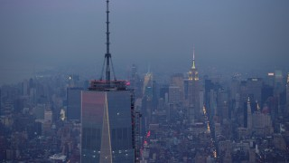 AX65_0216 - 5K stock footage aerial video track top of One World Trade Center in Lower Manhattan with Empire State Building in background, New York City, winter, twilight
