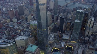 AX65_0219 - 5K stock footage aerial video tilt up side of Freedom Tower in Lower Manhattan, NYC, winter, twilight, with East River and Brooklyn in the background