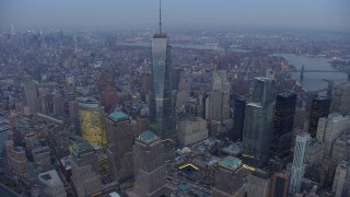 AX65_0227 - 5K stock footage aerial video orbit Freedom Tower and World Trade Center Memorial in Lower Manhattan, New York City, with a view across Manhattan, winter, twilight