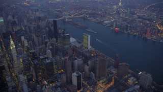 AX65_0247 - Aerial stock footage of United Nations, Midtown Manhattan skyscrapers, and the East River, New York City, winter, twilight