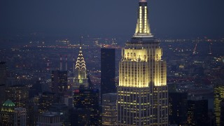 AX65_0254 - Aerial stock footage of Orbit Empire State Building in Midtown Manhattan with a view of the Chrysler Building, New York City, winter, twilight