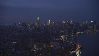 AX65_0265 - 5K stock footage aerial video of power plant with smoke stacks and the Midtown Manhattan skyline, New York City, winter, night