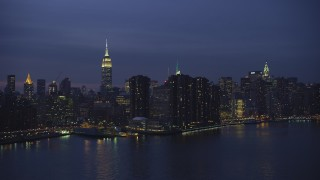 AX65_0268 - 5K stock footage aerial video of passing riverfront condos with Empire State Building in background, Midtown Manhattan, New York City, winter, night