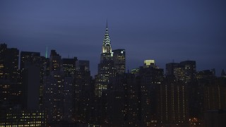 AX65_0272 - Aerial stock footage of The Chrysler Building and surrounding skyscrapers, Midtown Manhattan, New York City, winter, night