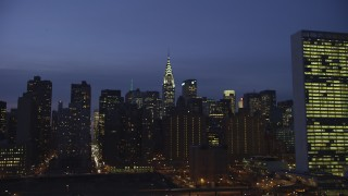 AX65_0273 - Aerial stock footage of View of the Chrysler Building, flyby the United Nations, Midtown Manhattan, New York City, winter, night