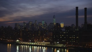 AX65_0280 - Aerial stock footage of Flyby public housing in East Village, with Lower Manhattan skyline in the background, New York City, winter, night